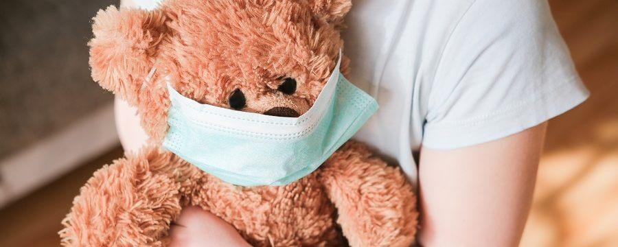 little girl holding teddy bear in medical mask
